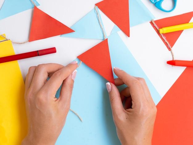 赤と青の紙で装飾を作る女性