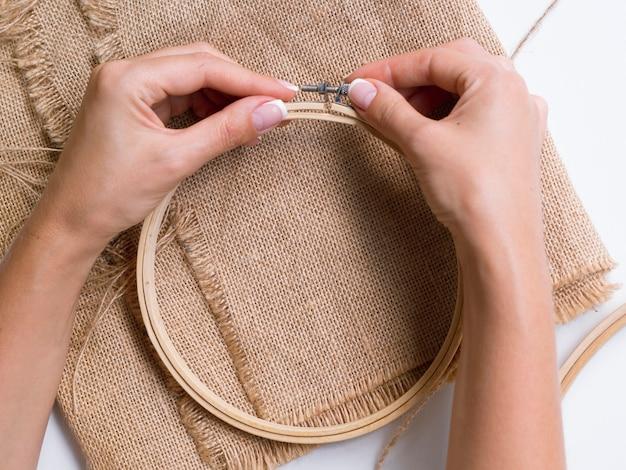 木製のリングから装飾を作る女性