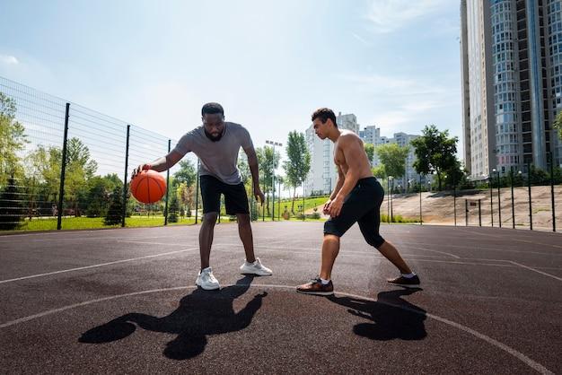 都市のバスケットボールのロングショットをして幸せな男性