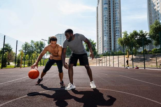 都市のバスケットボールで遊ぶ背の高い男性