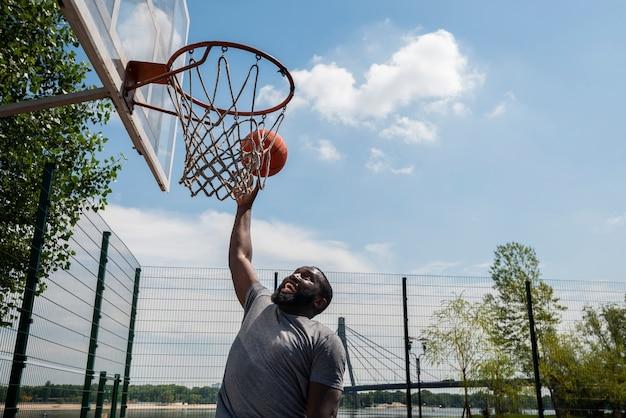 バスケットでゴールを決めるアフロ男