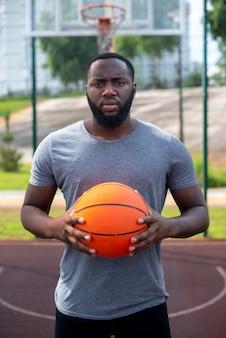 バスケットボールコートミディアムショットでボールを保持している男