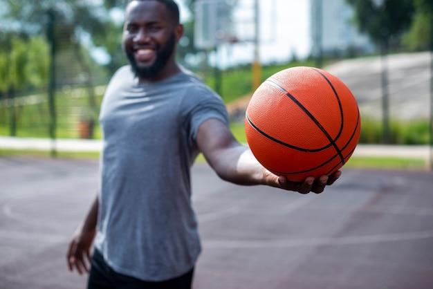 Молодой человек держит мяч среднего выстрела