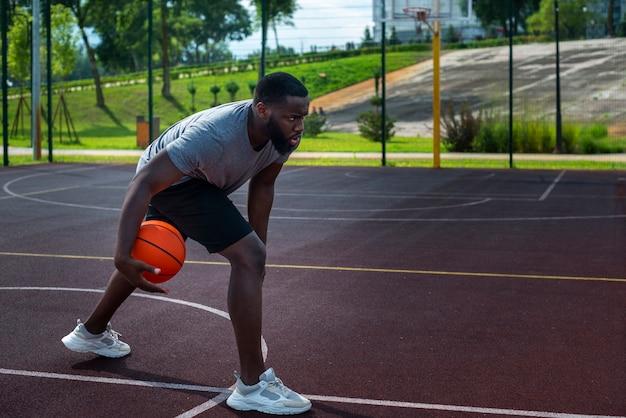 フィールドでバスケットボールをするアフロの男