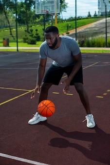 バスケットボールのロングショットをプレイアメリカのハンサムな男