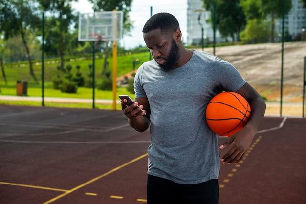 Бородатый мужчина смотрит на телефон среднего выстрела