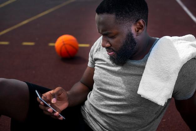 Американский спортсмен смотрит на телефон