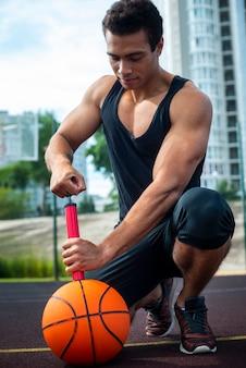 Сильный человек надувает мяч