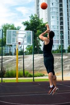 バスケットボールのフープにボールを投げる男