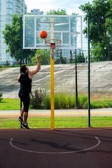 バスケットにボールを投げる男