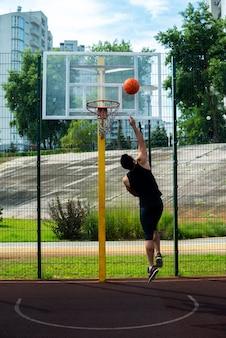 バスケットボールのフープでゴールを決めるスポーツマン