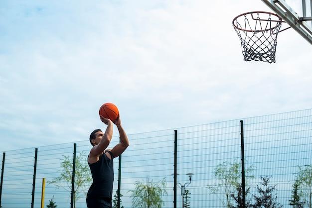 フープにボールを投げる男