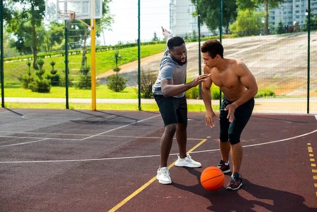 Агрессивный человек играет в баскетбол длинный выстрел