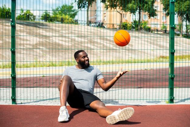 Человек бросает мяч в дальний выстрел