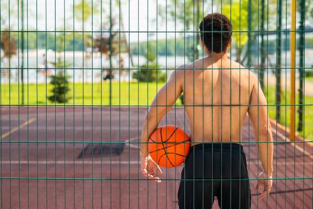 男はボールを保持し、フープを見て