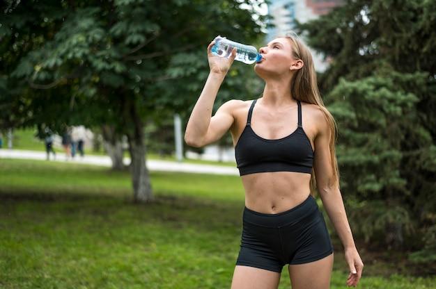 美しい女性飲料水ミディアムショット