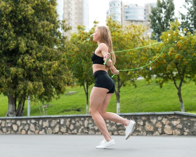 Спортивная женщина прыгает через скакалку