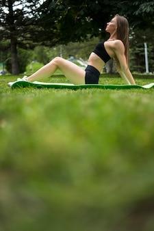 公園の低角度のビューで演習を行う女性