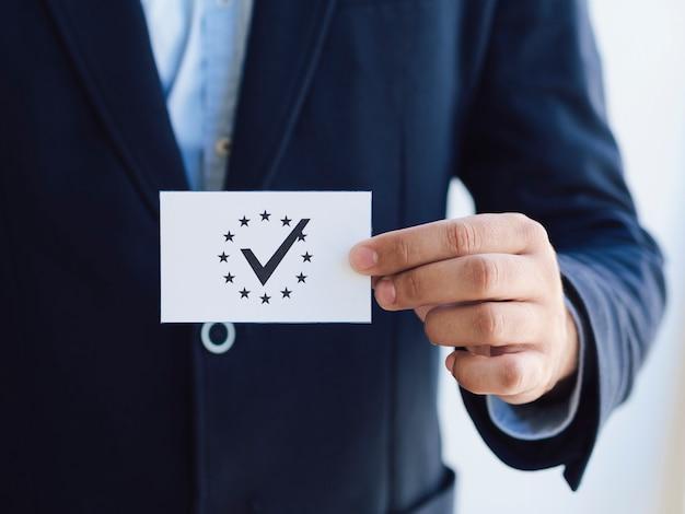Вид спереди мужчина держит избирательный бюллетень