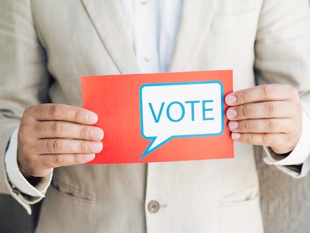 Мужчина в костюме держит голосующее сообщение