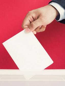 ボックスのモックアップに空の投票を置く男