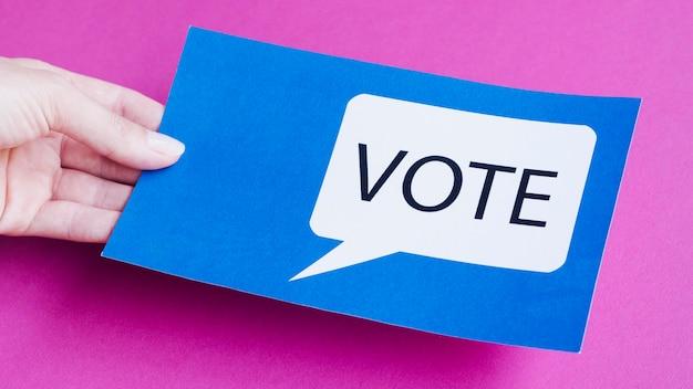 Человек высокого угла держа голубую карточку с пузырем речи голосования