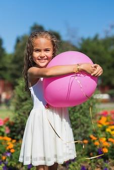 Вид спереди девушка держит воздушный шар