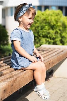Вид сбоку маленькой девочки на скамейке