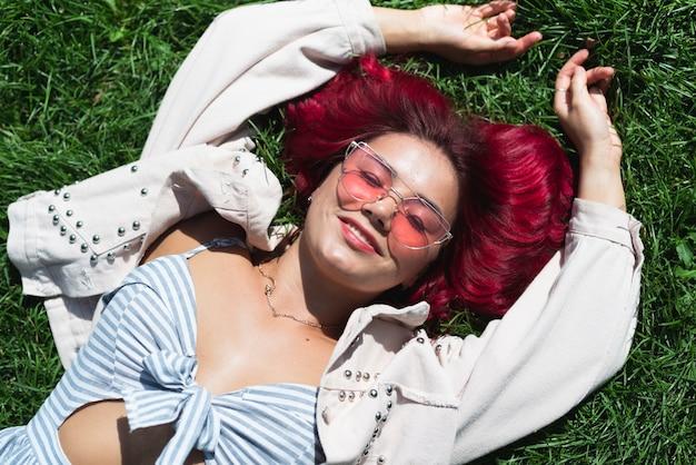 草で横になっている女性のミディアムショット