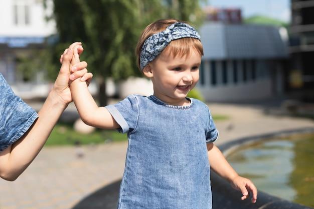 Милая маленькая девочка в парке с матерью