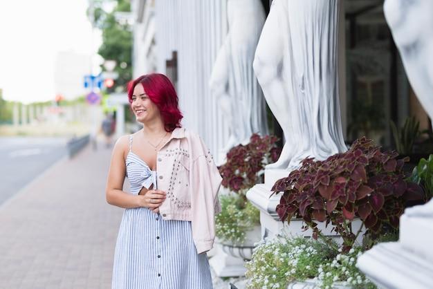 赤い髪と花を持つ女性