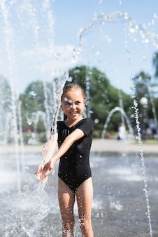 Милая девушка с удовольствием у фонтана