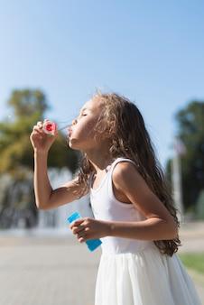 Вид сбоку девушка дует пузыри