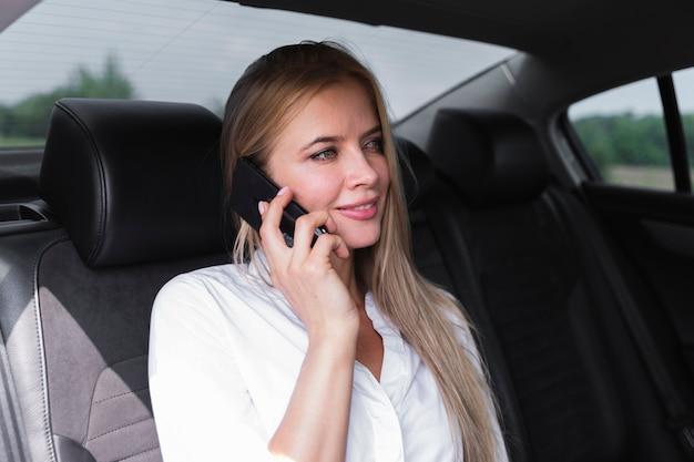電話で話している後部座席の女性