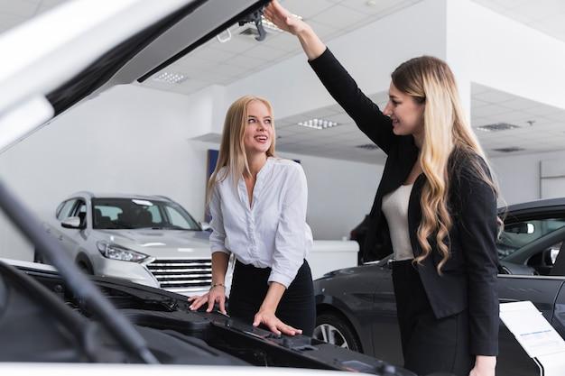 車のボンネットを開けてお互いを見ている女性