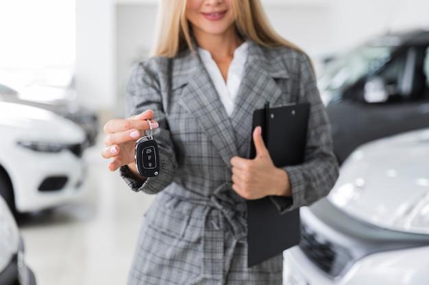 車のキーを保持している女性の正面図