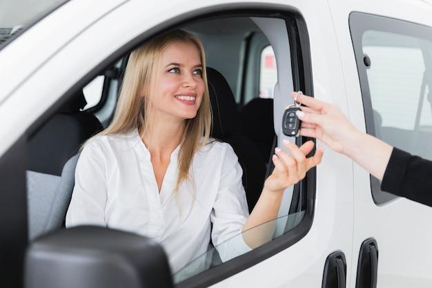 車のキーを受け取る笑顔の女性とのクローズアップショット