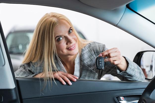 カメラを見て車のキーを保持している金髪の女性