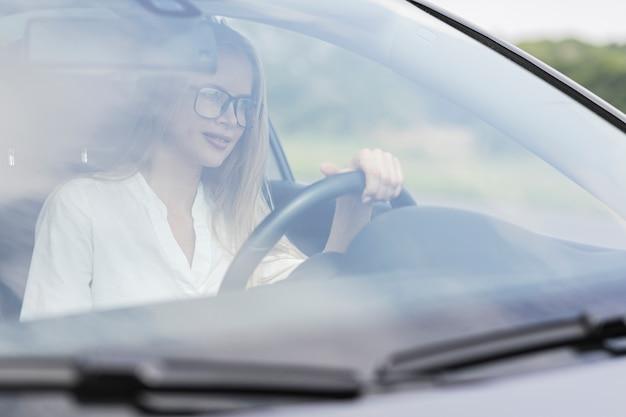 Крупным планом женщина за рулем автомобиля