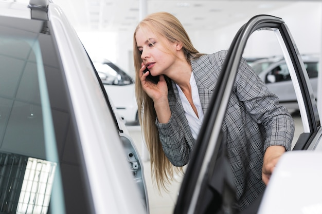 Молодая женщина смотрит в машину среднего выстрела