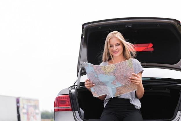 Сексуальная женщина ищет под капотом автомобиля