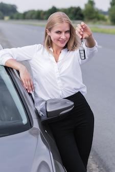 車のミディアムショットのキーを示す若い女性