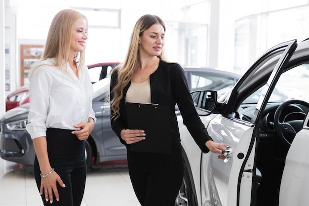Красивая женщина, открыв дверь автомобиля