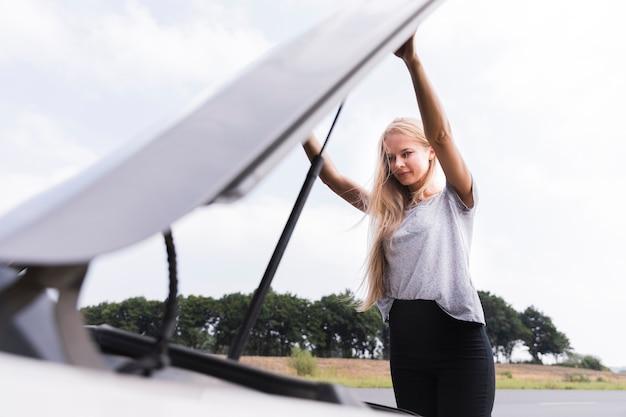 車のボンネットを開く女性