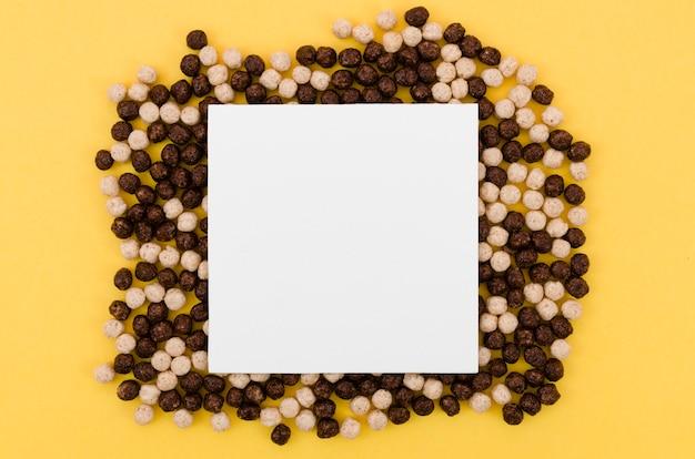 チョコレートシリアルに囲まれたコピースペースを持つ白いカード