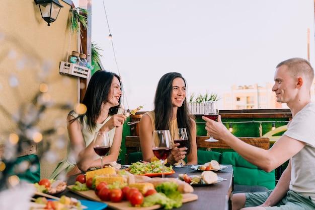 屋上でワインを乾杯する人々のグループ