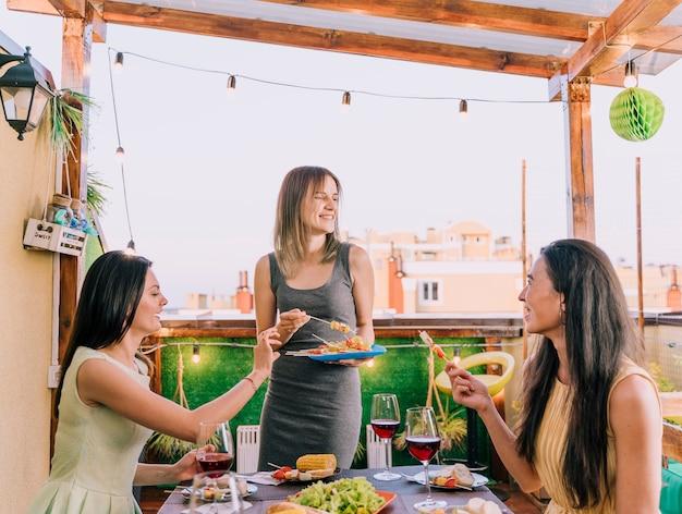 Девочки, хорошо проводящие время на вечеринке на крыше