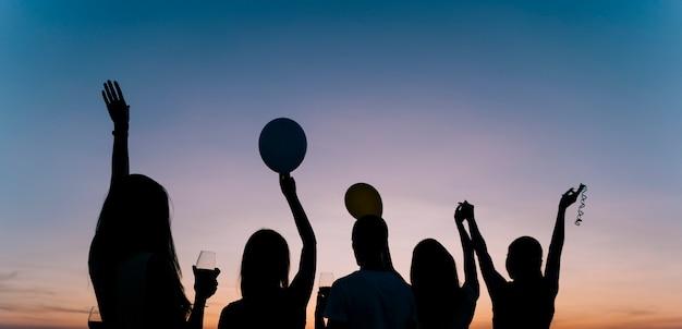 夜明けの屋上パーティーで踊る人々