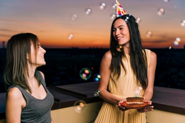 屋上パーティーにパーティーハットを持つ女性