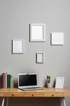 ノートパソコンとフォトフレーム付きの木製デスク